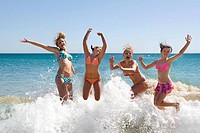 Teenage girls jumping in ocean