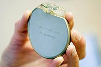 Heart pacemaker demonstrator held in a hand. Pacemakers are fitted in patients with a malfunctioning sinoatrial node, the part of the heart that initi...