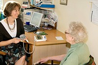 Blood pressure measurement. General practice doctor holding a cuff grey band after using it to take a woman´s blood pressure. The cuff is connected to...