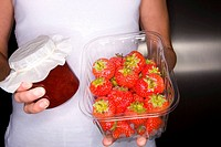 Close up of woman holding fresh strawberries and jam