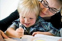 Mother with child drawing on book
