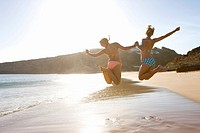 Teenage girls jumping in beach
