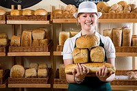 Portrait of baker in uniform holding loaves of bread