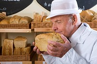 Portrait of baker in white uniform smelling loaf of bread