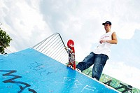 male teenager with skateboard on halfpipe