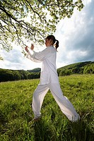young woman practising Tai Chi, grasp birds tail