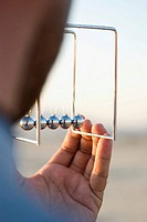 close-up of a businessman watching Newton's cradle pendulum