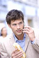 Young man holding sandwich and using mobile phone
