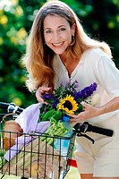 blonde woman with a bike and a flower bouquet