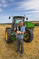 Farmer holding dog near tractor
