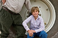 Boy sitting on rim of tractor wheel