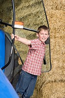 Portrait of boy leaning outside tractor next to hay