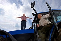 Farmer watching grandson stand on tractor hood