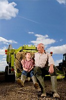 Farmer and grandson sitting on tractor with straw