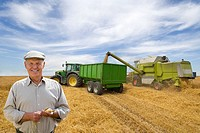 Portrait of farmer in barley field with combine in background