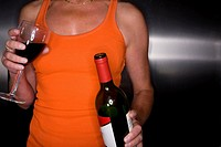 Close up of woman holding bottle and glass of red wine