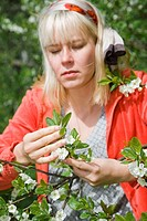 A woman is taking care of the garden in the summer.