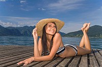 Young woman with sun shade and bikini bathing in the sun