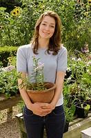 A portrait of female holding a plant pot