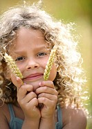 Young girl holds up ears of corn