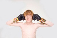 Redheaded boy wearing boxing gloves