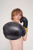 Redheaded boy wearing boxing gloves punching at camera