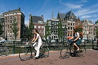 Two women cycling along canal, Amsterdam, Netherlands
