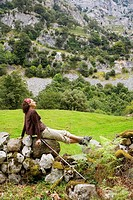 Young woman sit on a stone wall in the country  Ason valley, Cantabria, Spain, Europe