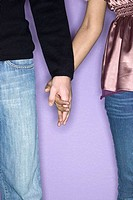 young mixed race couple in love holding hands in studio purple background Denver, Colorado, USA
