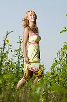 young confident pretty caucasian woman wearing summer dress in a field of sunflowers Loveland, Colorado, USA