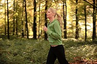 Young blond woman jogging in autumn forest