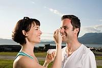 Couple applying suntan lotion