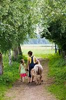 Sisters walking a shetland pony