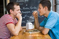 A gay couple having pizza