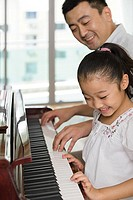 A father and daughter playing the piano