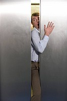Close_up of a businessman squeezing through doors of an elevator