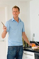 Portrait of a mid adult man holding a kitchen knife and smiling