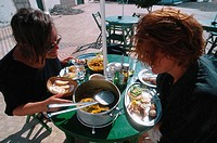Two women eating fish dish at outdoor seating of a bar at Puerto de la Luz, Jandia Peninsula, Fuerteventura