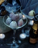 Close up of cocktail glass full of figs next to small bottle of Moet champagne.