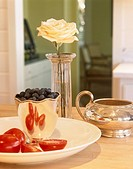 Single rose on wooden table, plate of halved tomatoes, container of olives,