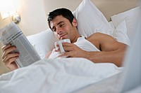 Man Reading and Drinking Coffee in Bed