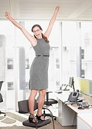 Businesswoman at desk cheering