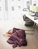 Businesswoman sleeping on office floor