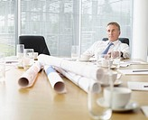 Businessman sitting at conference table with blueprints