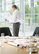 Businessman reviewing blueprints in conference room