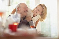 Woman hugging husband at dinner table
