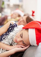 Woman in Santa hat sleeping on sofa