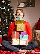 Man holding pile of Christmas gifts