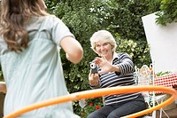 Grandmother taking photograph of granddaughter using hula hoop