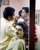 indian men in a barber shop getting facials